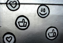 a white wall spray painted with facebook thumbs up symbols and smiley faces