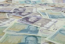 a pile of spread out five pound and twenty pound notes, covering the full image