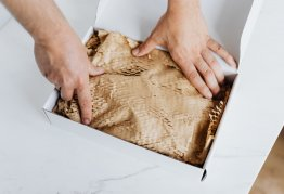 two hands reach into a box filled with packing materials