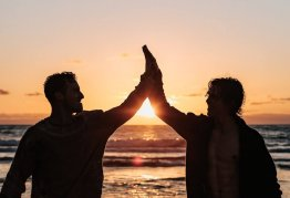 two men high fiving in silhouette against the sunset on a beach