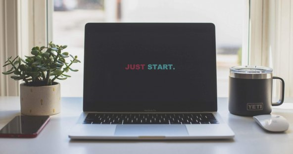 """a laptop sits on a desk in front of a bright window, the screen reads """"just start"""""""