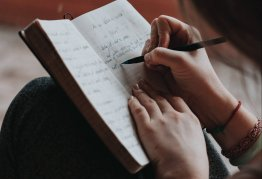a brunette girl handwrites small, but neat, notes in a notebook on her lap.