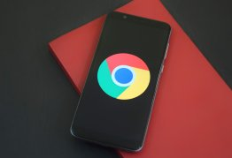 a smart phone lines on top of a red notebook, the screen displays a big google chrome logo, and nothing else
