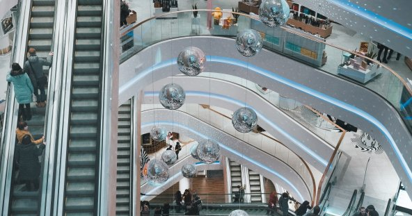 a birds eye view of a busy shopping centre, with an escalator to the left. there are silver disco balls hung at various heights from the ceiling