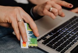 a person holding a bank card as they browse on a laptop