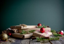 a pile of christmas presents wrapped in brown paper sit in front of a green wall