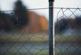 a wire fence with a sizeable hole in it