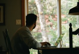 a man sits at a table with his laptop and stares longingly out the window at his garden