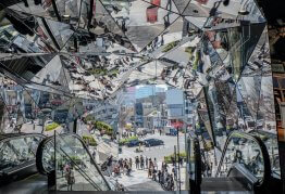 an angular and mirrored shopping center ceiling shows customers walking around